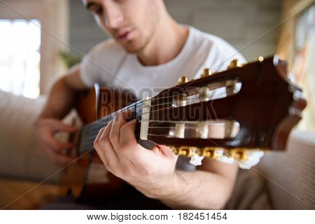 Close up shot of guitar in hands of man sitting on couch