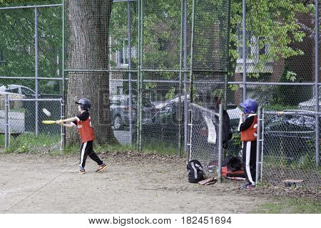 Montreal, Quebec - May 18, 2015 -- Wide view of little league baseball player hitting a ball as his team mate watches in a park in Montreal, Quebec on a bright day in Montreal.