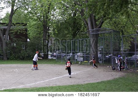 Montreal, Quebec - May 18, 2015 -- Wide view of little league baseball players practicing with their coaches in a park in Montreal, Quebec on a bright day in Montreal.