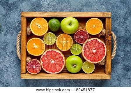 Different citrus fruit on a wooden box and grey concrete table. Food background. Healthy eating. Antioxidant, detox, dieting, clean eating, vegan, fitness or healthy lifestyle concept. Flat lay.