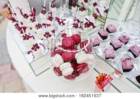 Red And White Macarons At Wedding Catering Table With Different Sweets.