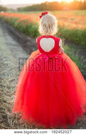girl model, childhood, fashion and summer concept - young blonde in a red dress standing with her back on the road next to the poppies field, on her back is a large cutout in the shape of a heart