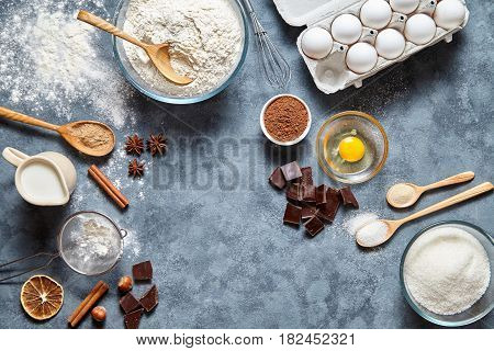 Brownie dough preparation cookie or chocolate cake recipe ingridients, sweet food flat lay top view on concrete kitchen table background. Work with butter, flour, sugar bakery cooking. Text space