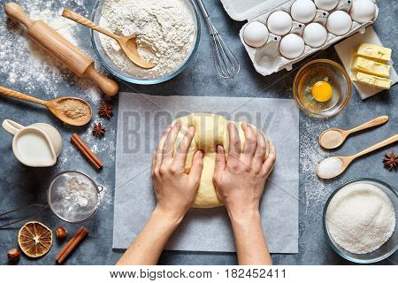 Baker chef preparing homemade dough bread, pizza or pie recipe ingridients, food flat lay on kitchen table background. Hands working with butter, milk, yeast, flour, eggs, bakery cooking. Top view