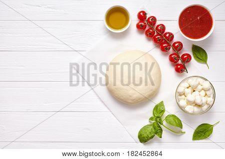 Raw pizza dough with ingredients: mozzarella, tomatoes sauce, basil, olive oil, cheese, spices. Italian margherita preparation on white wooden table. Italian pizza margarita