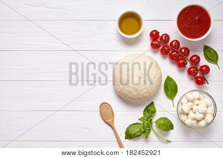 Raw pizza dough with baking ingredients: mozzarella cheese, tomatoes sauce, basil, olive oil, cheese, spices. Italian margherita preparation on white wooden table. Italian pizza margarita