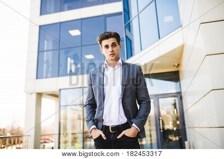 Elegant Handsome Young Businessman Hands In Pocket While Walking In Front Of Office Building