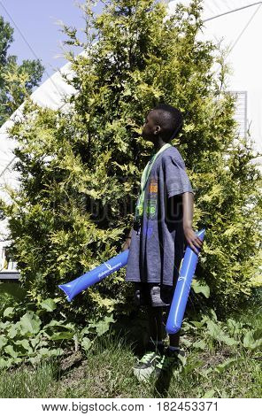 Laval, Quebec - June 14, 2015 - Close up vertical of a small African American boy looking to his right while standing and holding two plastic noise makers in his hands, with foliage in the background at the Nature Park, Laval, Quebec on a sunny day in Jun