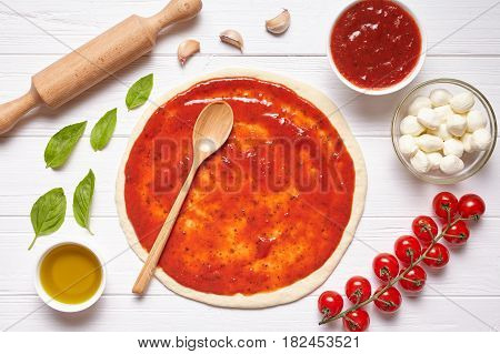 Pizza preparation. Baking ingredients on the kitchen table: rolled dough with tomatoes sauce, basil, olive oil, mozzarella cheese, spices. Italian food cuisine background pizza margherita