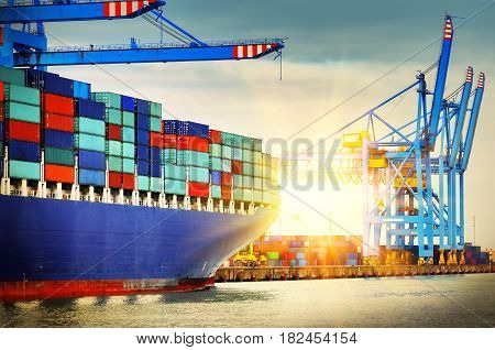 Container ship with full of cargo entering a port at sunset. Transportation background