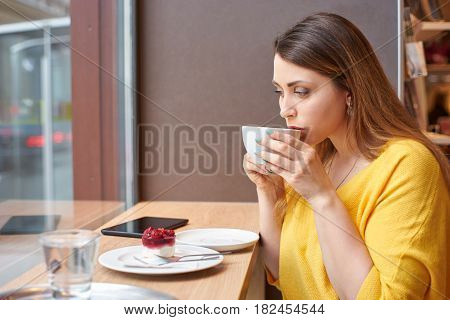 A young woman is taking a sip of coffee at the table with raspberry cake, glass of water and tablett on it. The scene is next to a window.
