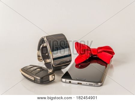 smartphone with smartwatch and car key exclusive black set white background red bow