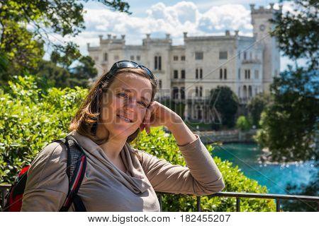 Attractive brunette posing infront of Miramare castle. Tourist exploring Italy.