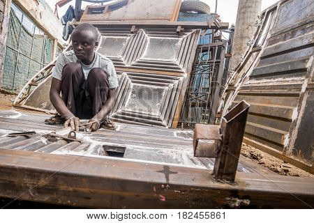 Nairobi Kenya - December 2 2016: Worker at welding workshop using sandpaper