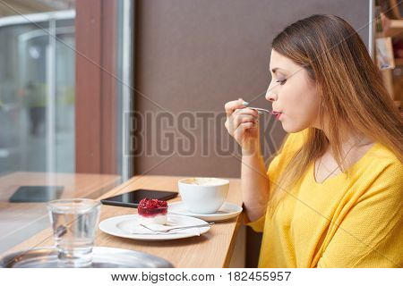 A young woman eating delicious raspberry cake at the table next to a window with cup of coffee, glass of water and tablett on it.