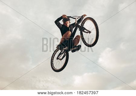 A person on trial bicycle flying over the camera. Horizontal outdoors shot.