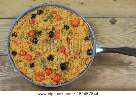 Healthy Vegetarian Mediterranean Style meal of rice onion small cherry tomatoes (cut in half and whole) and black olives seasoned with parsley flakes and red pepper baked in a pot