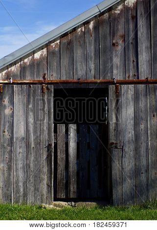 Old grey weathered open barn door with gate on rural farm.