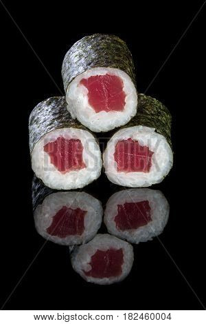 Sushi maki with tuna on a black backround with reflection. Asian food