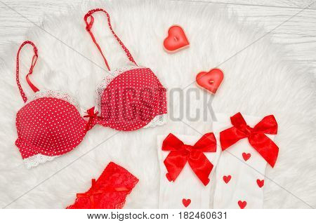 Fashion concept. Red bra and white stockings with bows candles in the shape of a heart on a white fur. top view