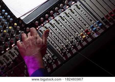 Sound mixer. Professional audio mixing console with lights buttons faders and sliders. With hand