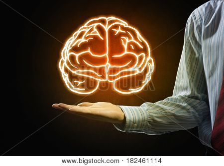 Close up of businessman hand holding brain in palm
