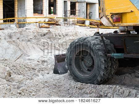 Grader blade pushing the sand on the construction site.