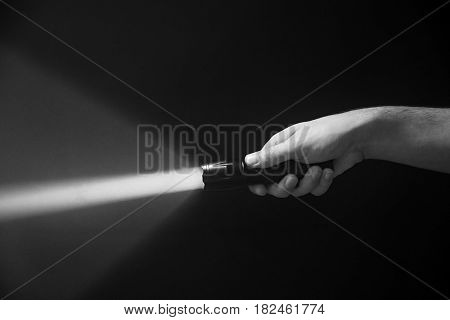 The Flashlight In The Man's Hand From The Right Side Of The Frame In Black And White Color Isolated