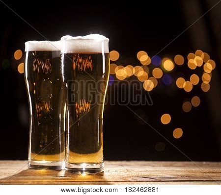 Two Glasses Of Beer On Bar Lights Background