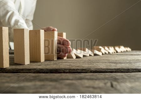 Man in white shirt stopping domino effect on wooden table. Business success concept.