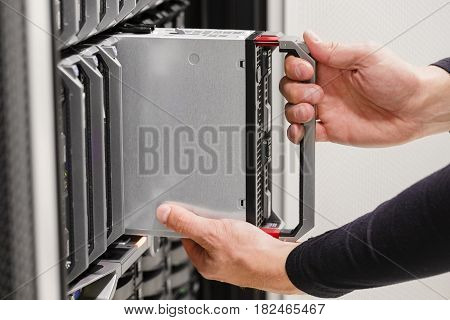 It engineer or consultant working with installation of a blade server cluster in data rack. Shot in enterprise datacenter.