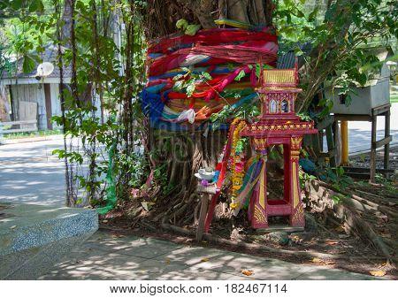 traditional Thai Spirit house near big tree in Thailand