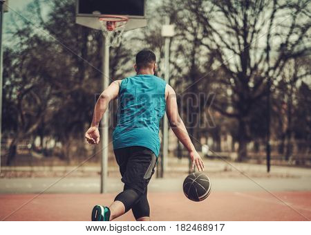 African-american streetball player practicing outdoors
