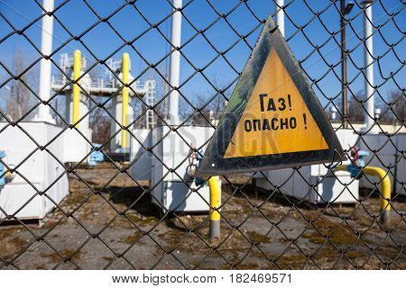 Gas! Dangerous! (metal sign with Russian inscription) on the metal mesh fence of the gas compressor station. Close-up.
