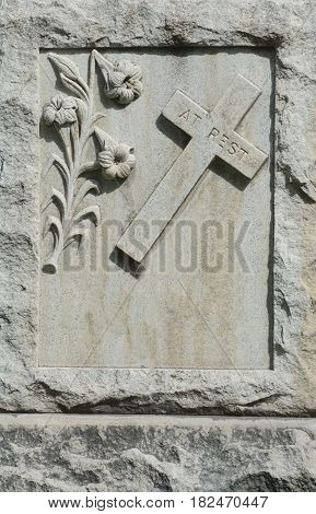 Close up of Christian gravestone with engraved cross with words