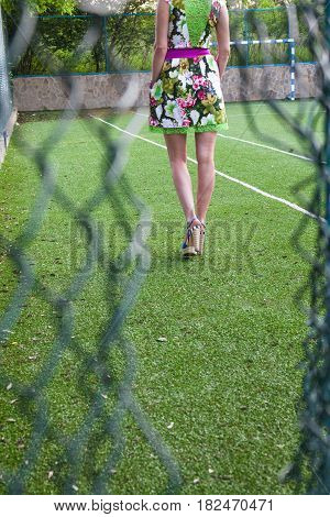 Young attractive woman on the soccer field behind the damaged metal mesh fence.