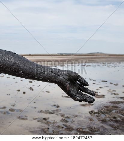 Woman's hand smeared with black healing mud. Close-up.