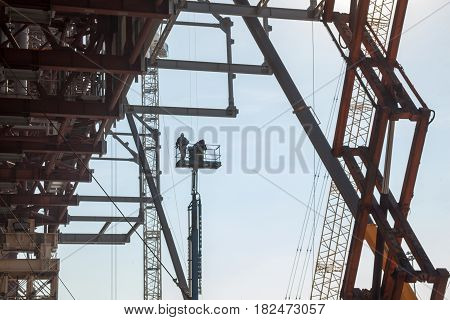 Metal scaffolding cranes and builders on the elevating work platform on the construction site.