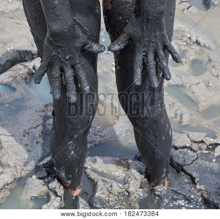 Woman's hands and legs smeared with black healing mud.