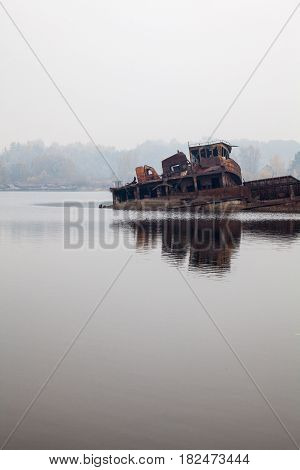 Old rusty sunken ship in water in a foggy day.