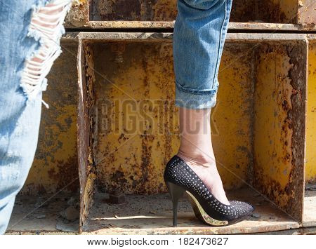 Woman's legs in ragged jeans and black stiletto-heeled shoes near the rusty metal industrial wall. Foot. Close-up.