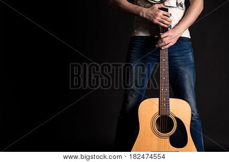 Guitarist holding two hands with an acoustic guitar