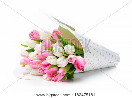 Bunch of tulips in paper bag over white background