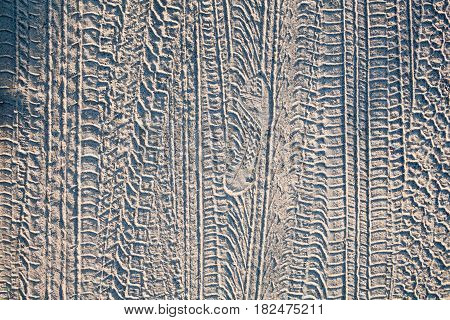 Wheel tracks and boot print on the ground on the dirt road.