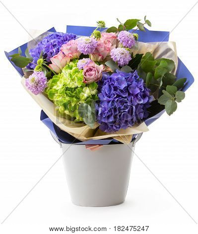 Bouquet of colorful flowers in decorative bucket over white background