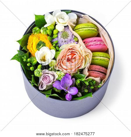 Gift box with macaroons and flowers over white view from above