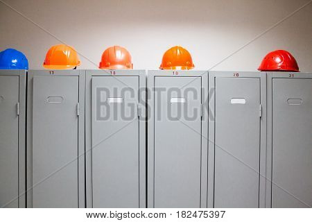 Metal lockers and plastic hard hats in the cloakroom of the industrial plant.