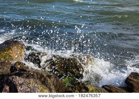 Waves breaking onto a stony seashore. Close-up.