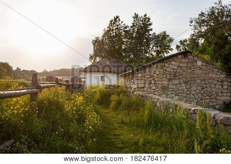 Ukrainian village. Path in the grass. Wooden fence. Wattle and daub and sandstone houses. Rural landscape.