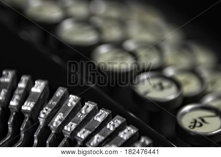 Vintage Keyboarding: Classic 1940's typewriter with bokeh keyboard and black background. Suitable for placement in business offices and hotel rooms that cater to a business clientele.
